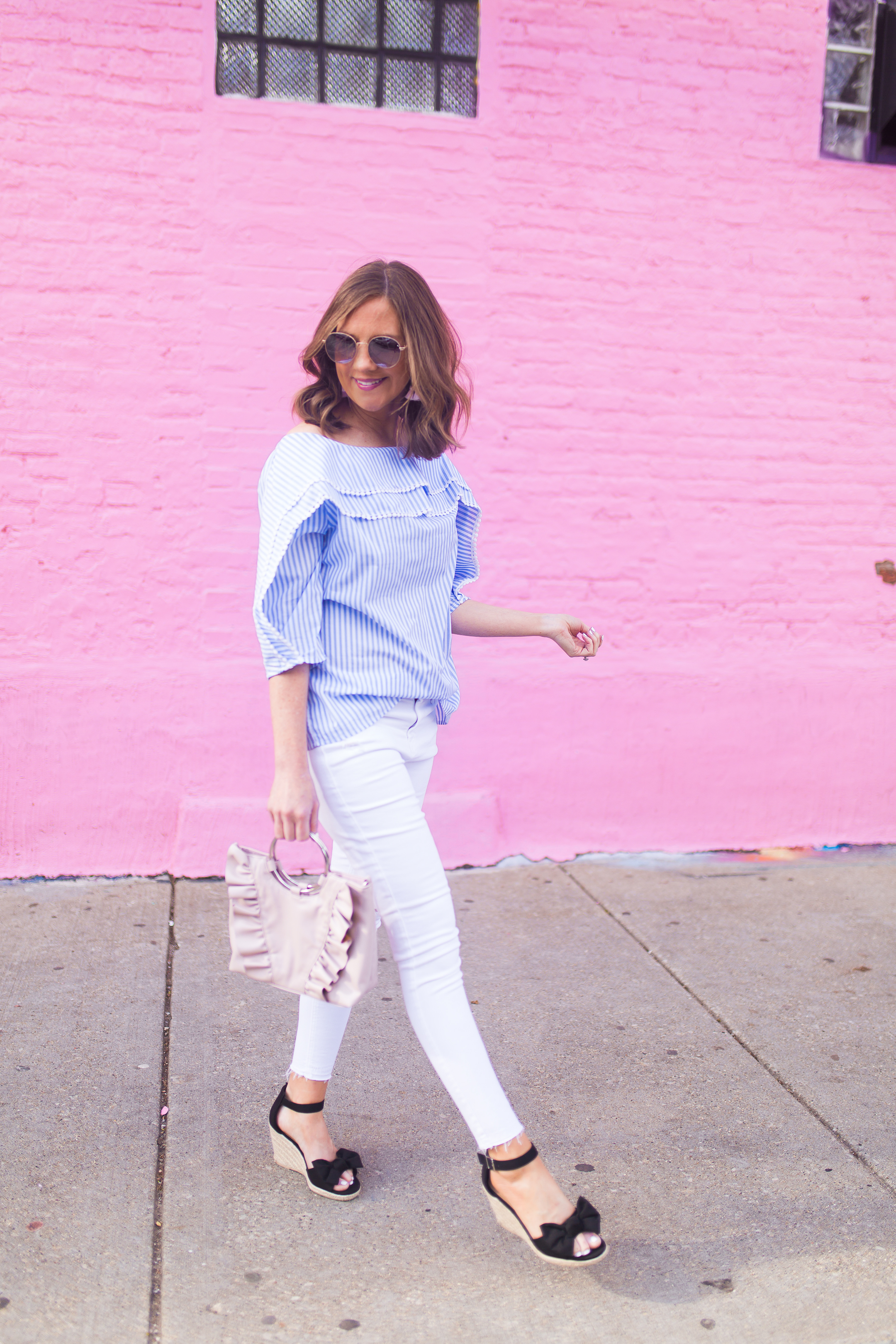 blue white pinstriped off the shoulder blouse with mini pompom trim, pink wall Chicago, bow wedges, ruffled pink bag with ring handle