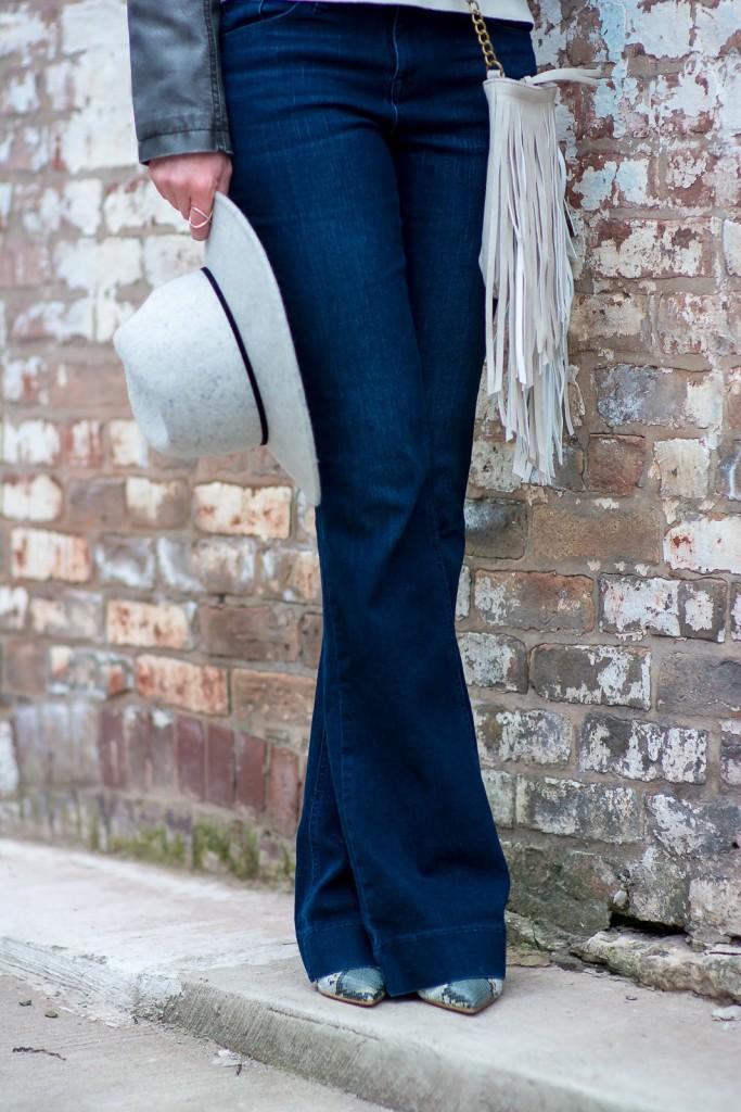 grown up boho outfit, fringe bag, grey fedora, vegan gay leather jacket, snakeskin heels, zara snakeskin heels, beige fringe snood, intermix scarf, flared jeans, target flared jeans, j brand jeans look for less