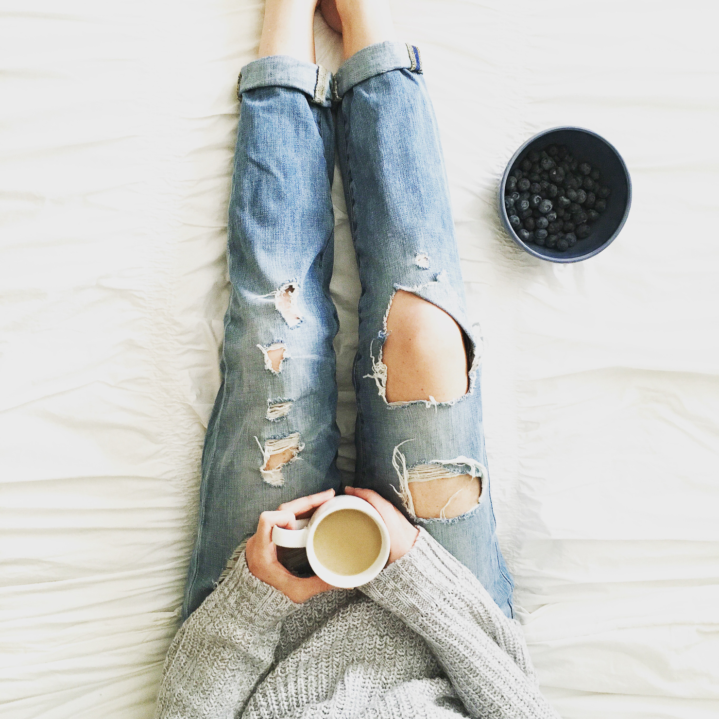 grey-sweater-distresse-boyfriend-jeans-coffee-in-bed-bowl-of-blueberries