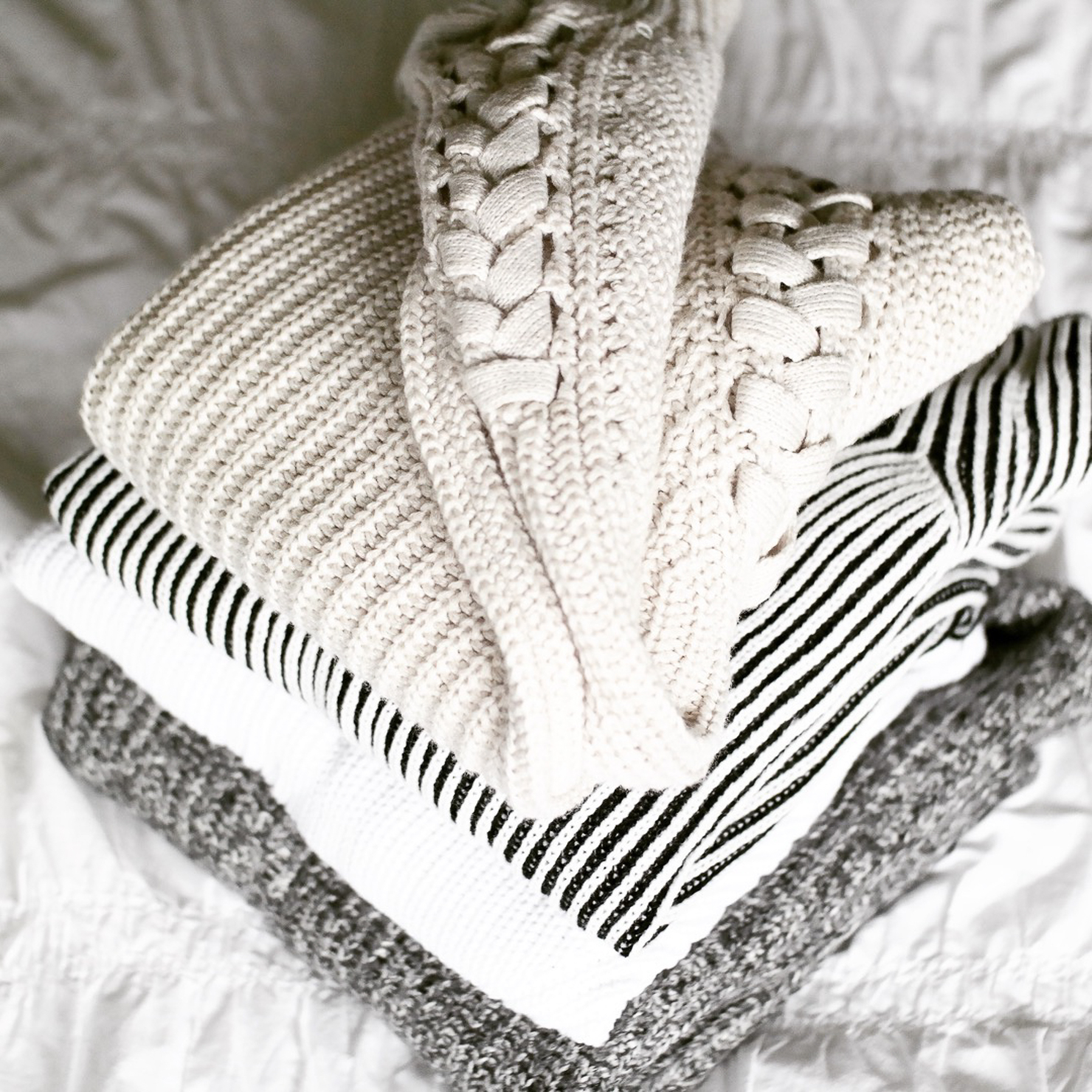 stack-of-cozy-sweaters-on-bed