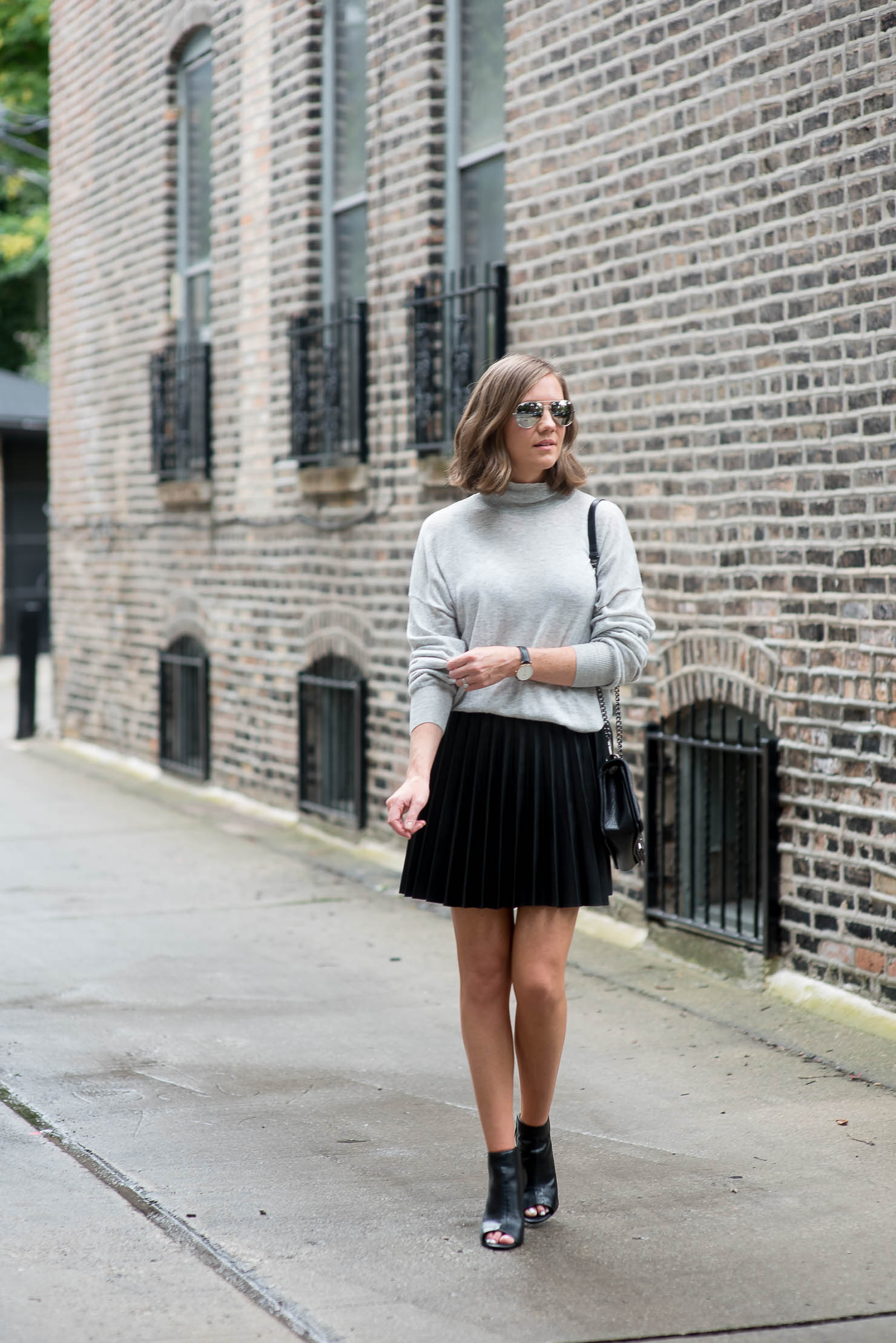 why-minimalist-style-need-not-be-boring-pleated-leather-mini-skirt-grey-slouchy-sweater-peep-toe-booties